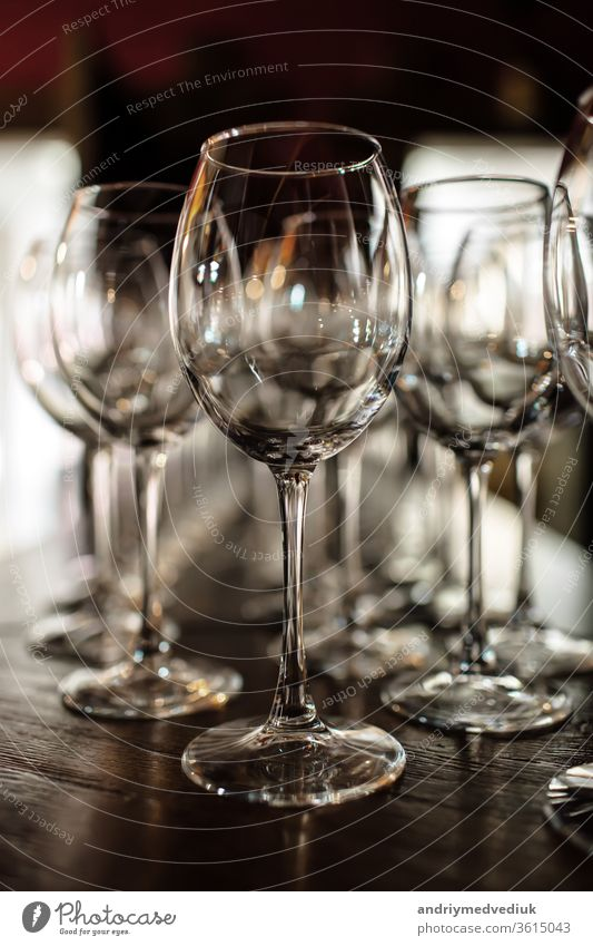 empty wine glasses. Beautiful new glasses for wine from glass stand in even rows on a wooden table in a restaurant. selective focus alcohol bar celebration