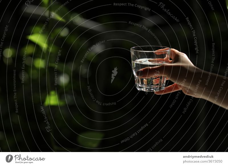 Woman holding a glass of water on a dark background. glass of pure water in hand. Healthy Lifestyle. ecology clean clear arm beverage fresh human isolated