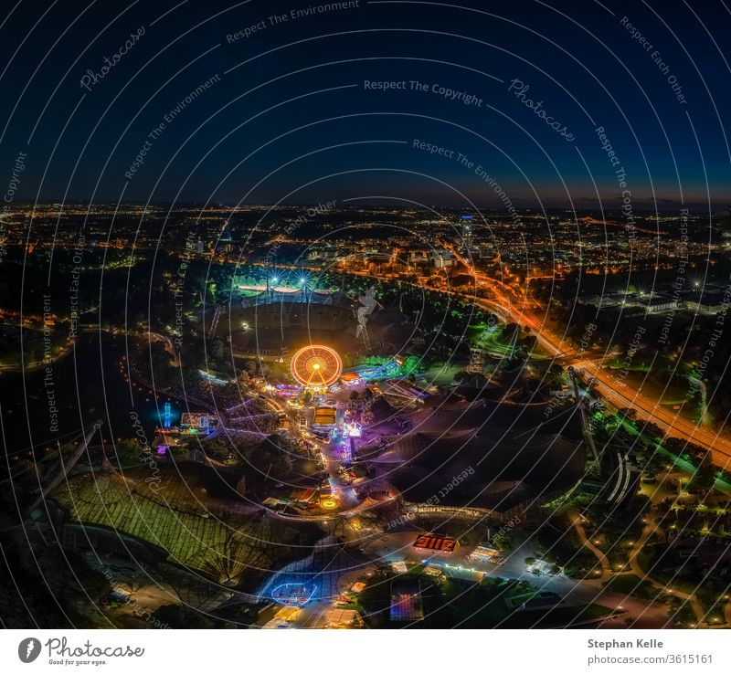 an impressive night view photo over Munich from the Olympic Tower at the ImPark festival at night with an illuminated ferris wheel. munich fun muenchen