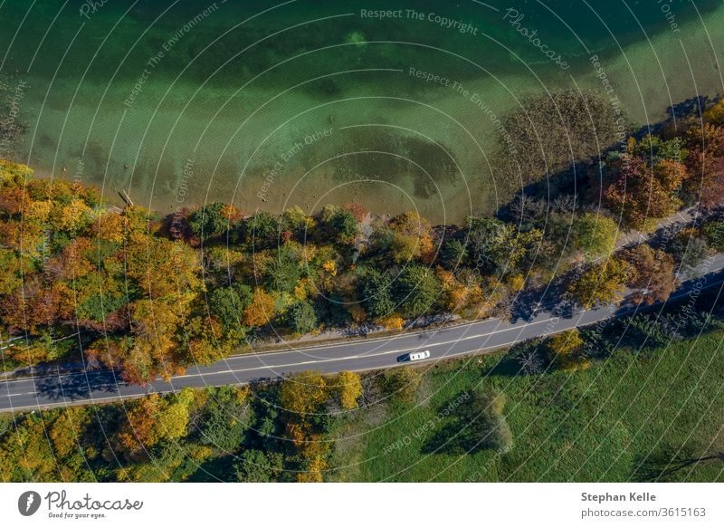 Aerial view of road with a car in autumn forest next to a touquise colored lake. top countryside drone highway travel beautiful transportation landscape aerial