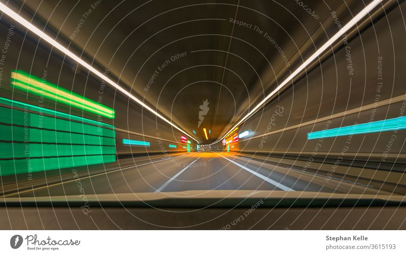 Fast moving with my car through a tunnel with leading lines and lights and blur effect. Abstract alcohol artificial light asphalt automobile blurred colors dark