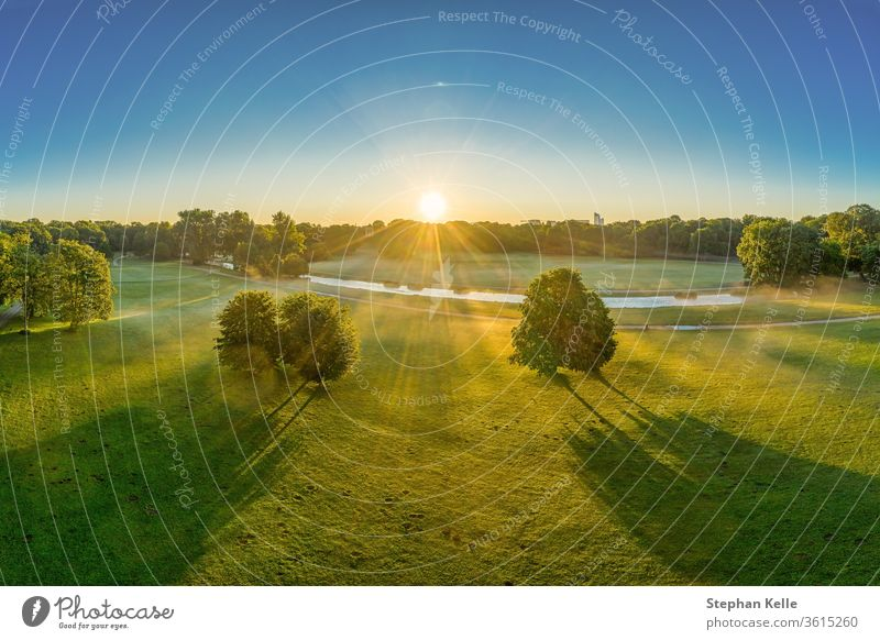 Wonderful sunrise over the English Garden in Munich. Sunbeams are shining through the trees sunbeam english authentic garden nature minga misty meadow green