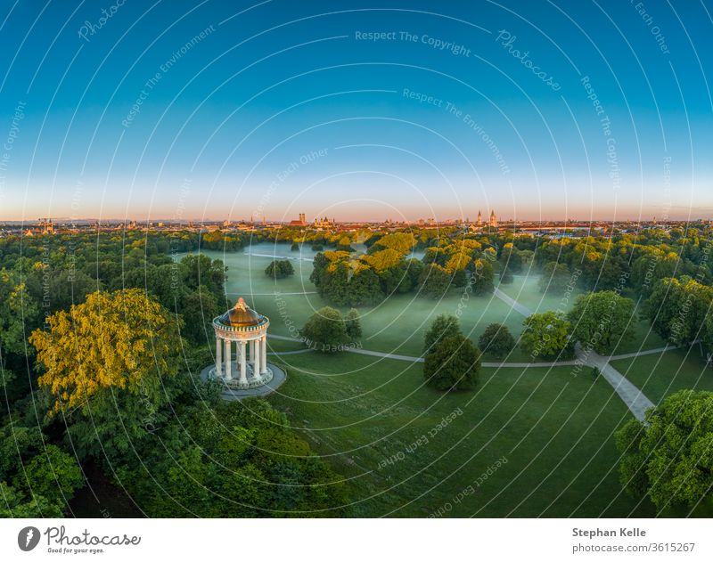 Wonderful aerial view over the Englischer Garten of the bavarian capital Munich at the early morning with fog in the green park. misty munich tree sky sun