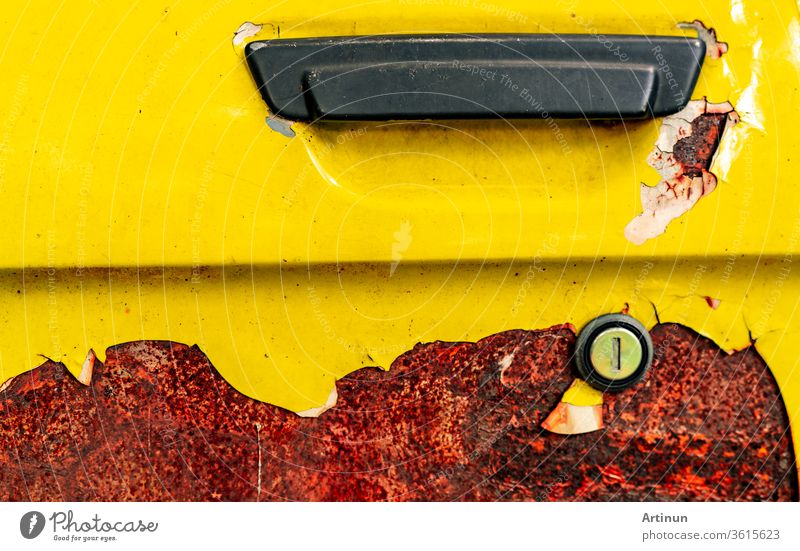 Close up old car door with rusty. Abandoned rusty yellow car with black handle. Car coloring is peeling. Old and rusted automobile door texture background. Cracked paint. Hole of auto key.