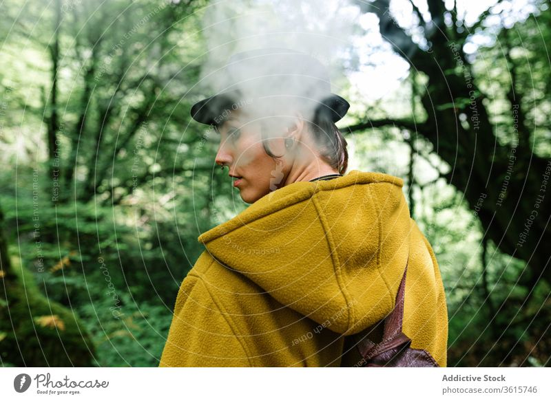 Woman smoking in green forest woman smoke travel style informal exhale tree countryside alternative subculture outerwear relax female nature trendy nicotine