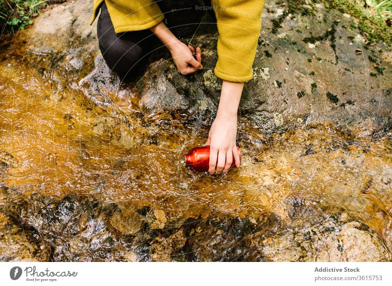 Anonymous woman taking water from brook in forest bottle clean style green female outerwear creek nature relax lifestyle countryside informal thirsty