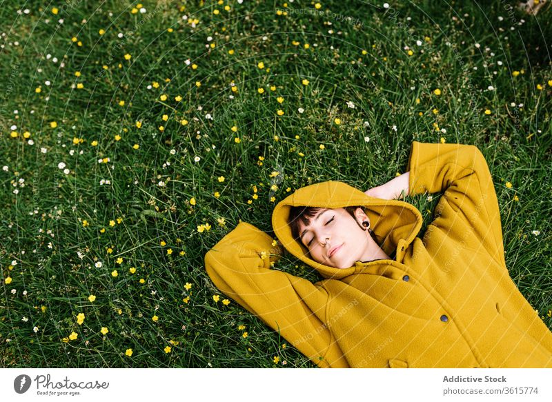 Relaxed informal woman lying on meadow relax enjoy summer lawn green piercing brutal carefree female grass rest nature flower cheerful holiday weekend smile