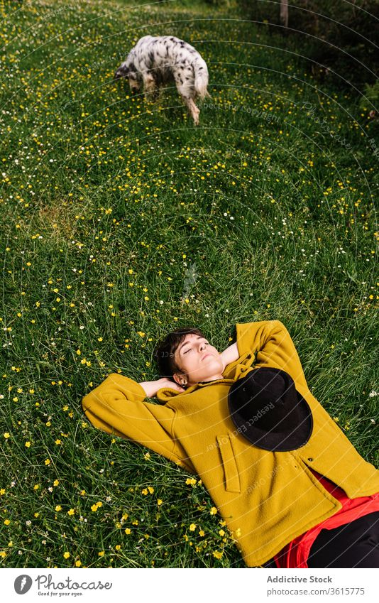 Cheerful woman with dog on meadow enjoy sun together lying cheerful flower content female asturias spain canine nature happy animal pet summer domestic