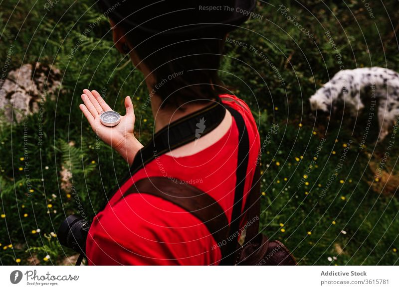 Unrecognizable female tourist navigating by compass navigate traveler woman orientate holiday meadow find backpack asturias spain style photo camera wanderlust