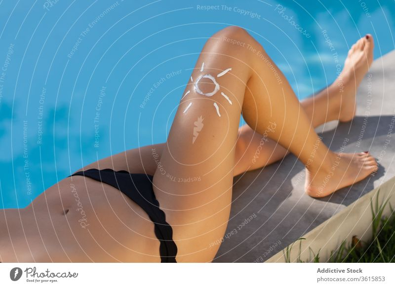 Woman applying sunscreen near pool woman sunbath poolside summer tan cream female leg relax rest holiday suntan recreation summertime protect swimwear swimming