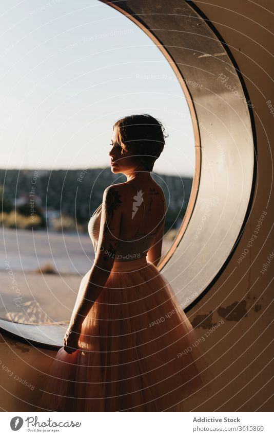 Relaxed female dancer looking at round hole woman grace relax dream pensive serene art creative window nature elegant slim sensual tranquil rest calm fantasy