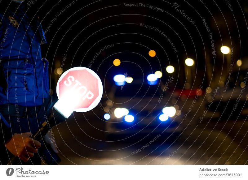 Police officer with stop sign police control car night law enforcement policeman male illuminate patrol glow siren flash light automobile vehicle transport dark