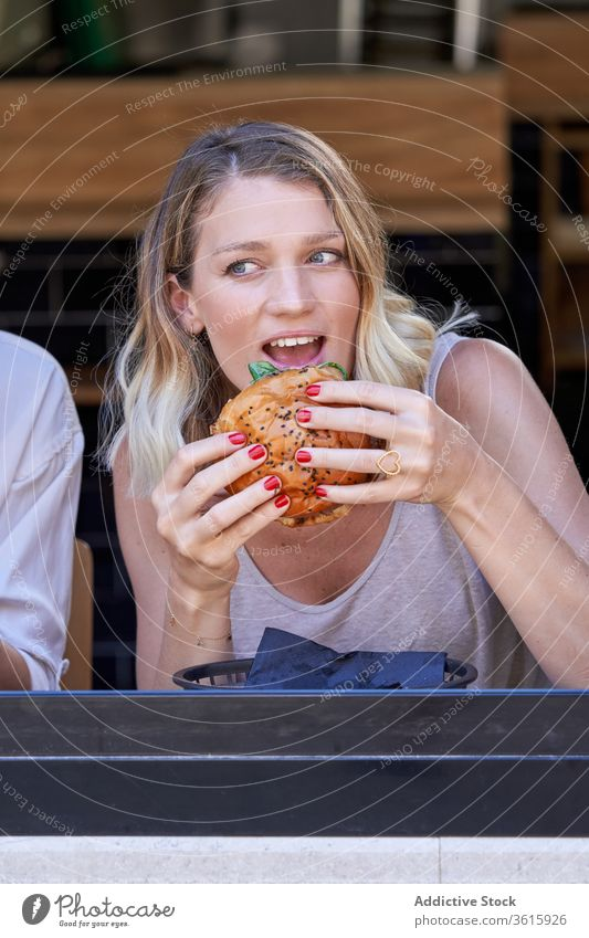Amazed woman eating meal in cafe excited together window lifestyle share burger enjoy meeting grimace lunch expressive restaurant modern contemporary female