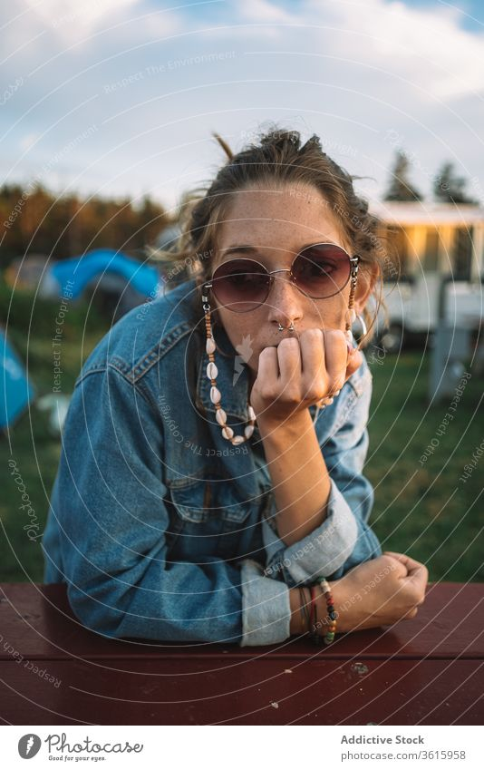 Woman relaxing in camping area hippie campsite woman travel sunset peaceful summer vacation female calm wooden table rest holiday camper tranquil serene enjoy