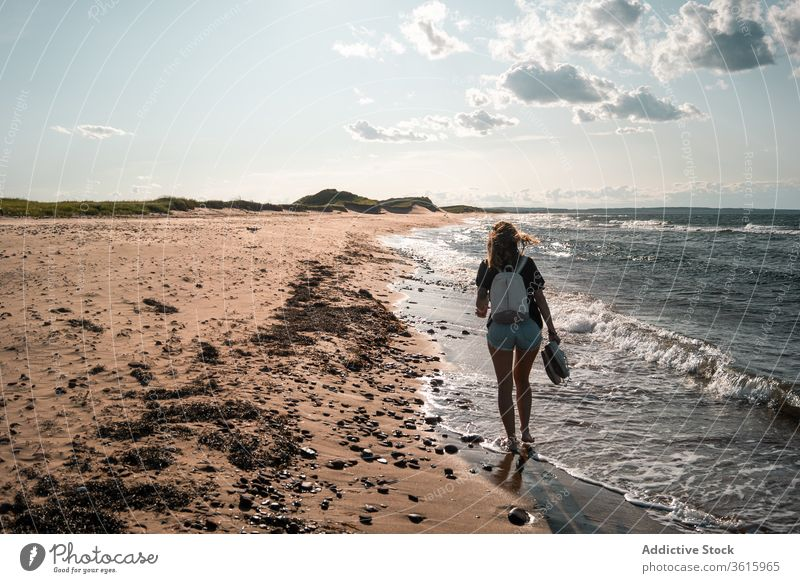 Traveling woman walking along seashore seaside vacation beach tourist summer sunny travel female barefoot journey holiday trip weekend idyllic seascape coast