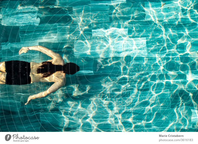 A man swimming alone in the pool showing the concept of staying fit in the new normal lifestyle due to the covid-19 pandemic social distancing