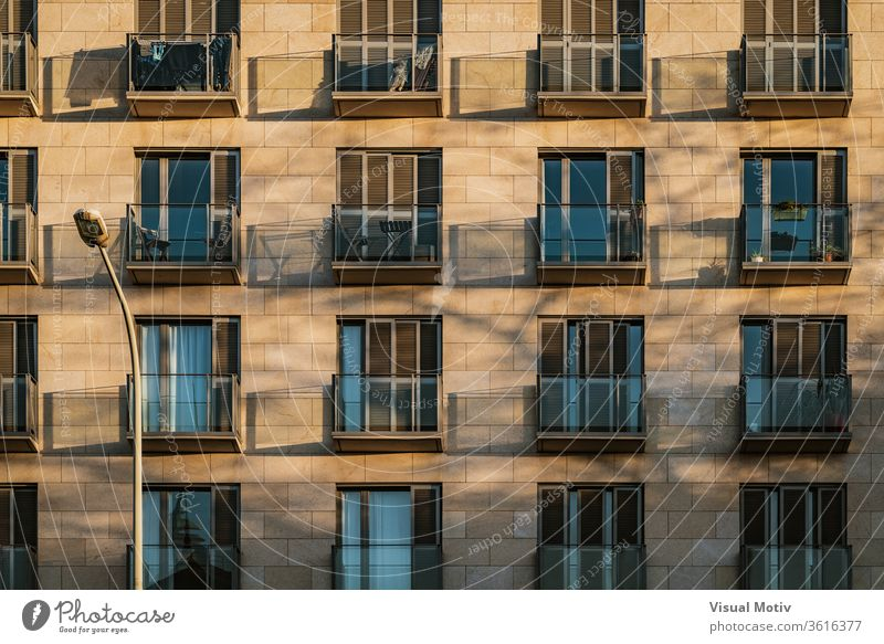 Shadows of modern balconies over a stone facade at the afternoon light building shadow balcony exterior apartment contemporary architecture construction