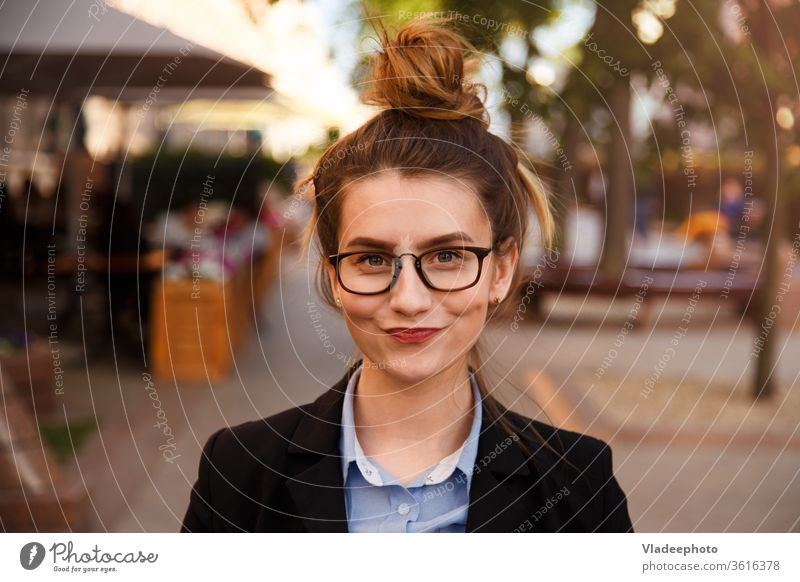 Young caucasian businesswoman in glasses smiling pursed lips. suit happy person portrait female young beautiful outdoor girl cute fashion pretty happiness