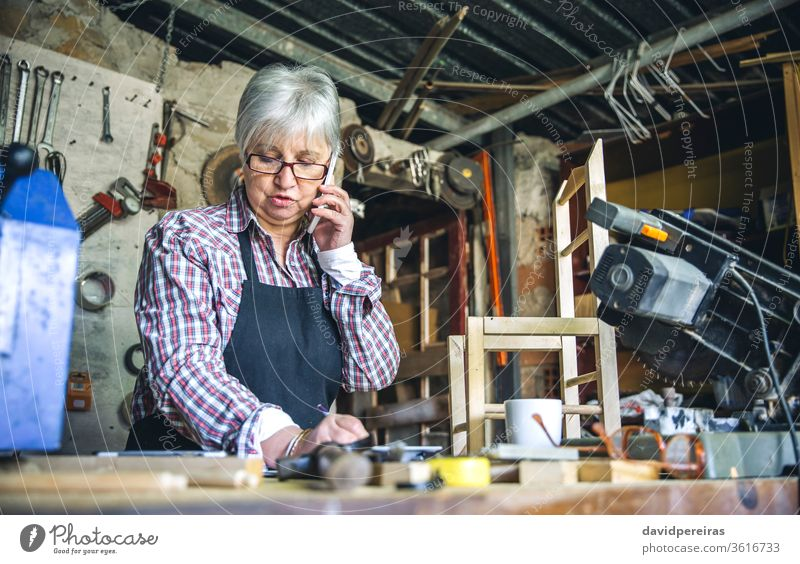 Female carpenter in her workshop woman senior talking mobile custom made business waist up carpentry work bench mature writing wood worker craft occupation