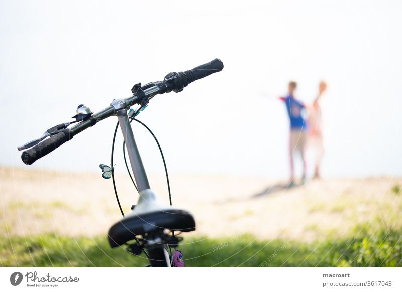 bicycle tour Cycling tour Bicycle Driving children Playing out Nature Landscape blurred Saddle Handlebars Butterfly Close-up Trip Couple couple company