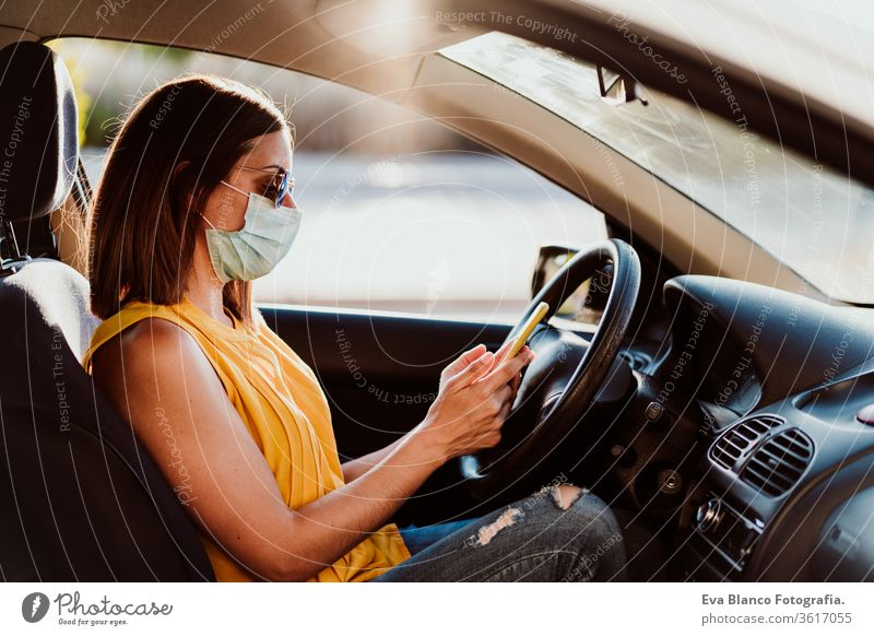 young woman in a car using mobile phone, wearing protective mask. Summer season. prevention corona virus concept technology summer communication disinfection