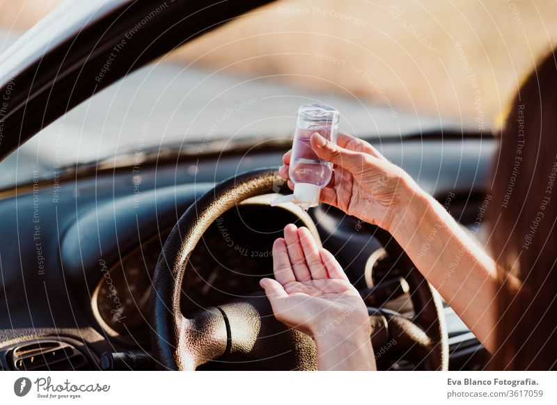 unrecognizable woman using disinfectant alcohol gel in a car before driving. Clean hands concept clean virus corona pump transportation outbreak service
