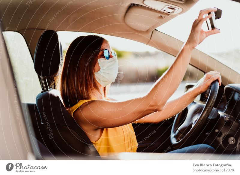 young woman in a car wearing protective mask. Summer season. prevention corona virus concept pandemic covid driving driver travel summer sunset trip adult