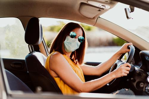young woman in a car with a protective mask. Summer season. Concept for the prevention of the coronavirus Woman Car Face mask Virus pandemic Corona virus COVID