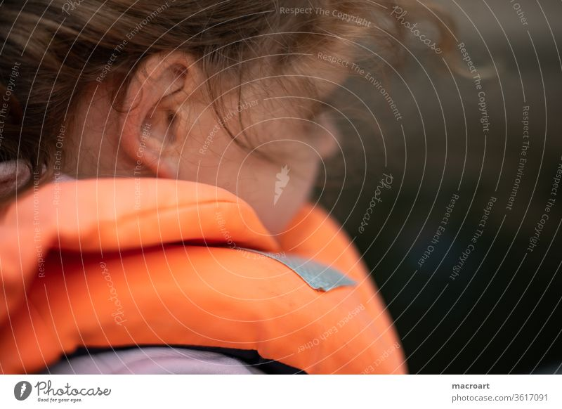 Child with life jacket girl curly-headed Life jacket Vest Safety Water Body of water Close-up Ear portrait Orange