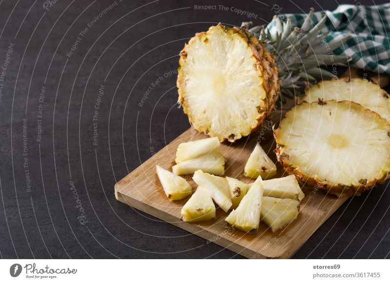 Fresh pineapple slices on cutting board and black background. Copy space ananas dessert diet fresh fruit healthy juicy nutrition organic slate sweet tropical