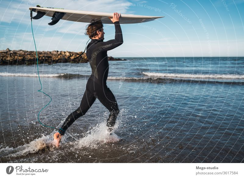 Surfer entering into the water with his surfboard. man sport surfing sea surfer ocean outdoors athletic scenic coastline waves background adventure sports