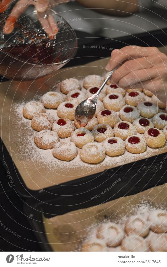 Christmas bakery: Filling a woman's hands with a teaspoon of currant jelly in angel's eyes, also called hussar doughnuts | Anticipation Cookie Christmas baking
