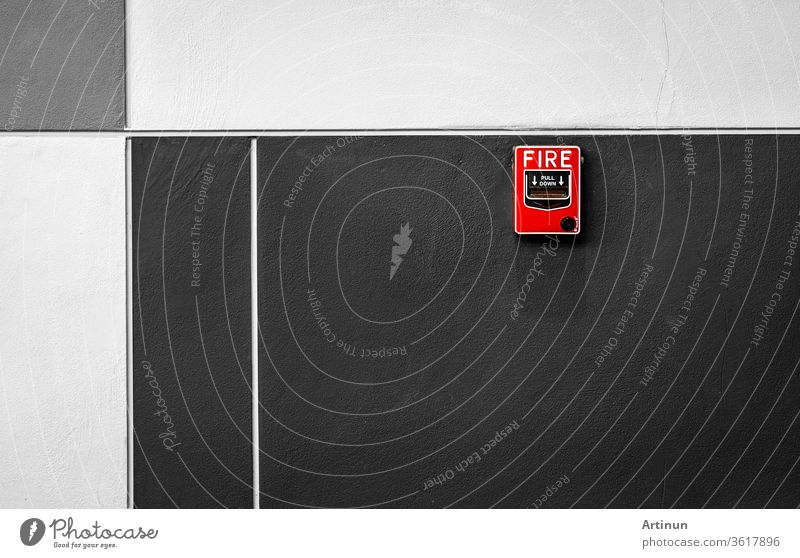 Fire alarm on black and white concrete wall. Warning and security system. Emergency equipment for safety alert. Red box of fire alarm on wall of school, hospital, factory, office, apartment, or home.