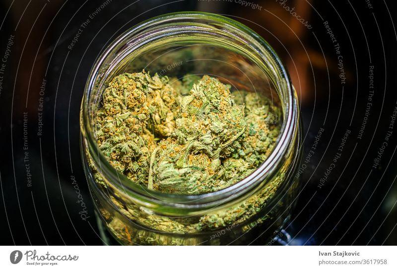 Cannabis flower buds in glass jar against dark background pot joint crime grinder cannabis addiction ganja smoking drug herb wild plant problem leaf herbal