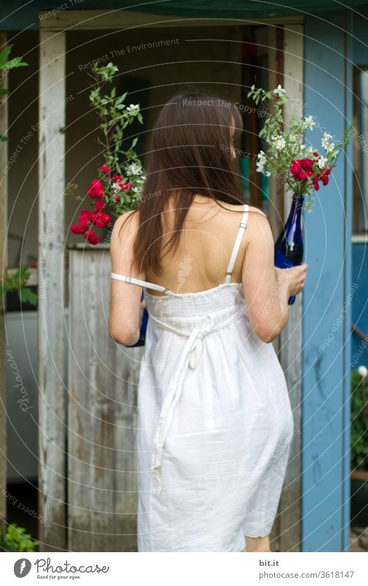 Rear view of a young woman in a white summer dress, holding a bouquet of flowers in a blue glass bottle in her hand. Party guest in a strap dress brings flowers to the summer party as a surprise. Young bride in brood dress.hippie girl at summer solstice in Sweden.
