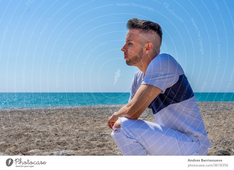 Young man in white pants and modern styling posing on the beach of the Mediterranean Sea in Burriana pleasure holiday toned fashion sky tourist pose wind tanned