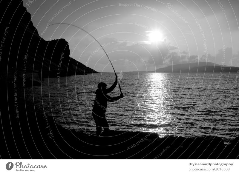 Young man fishing with feathers for mackerel B+W isle of mull scotland black white black and white fishing feathers fishing rod line hunting sport silhouette