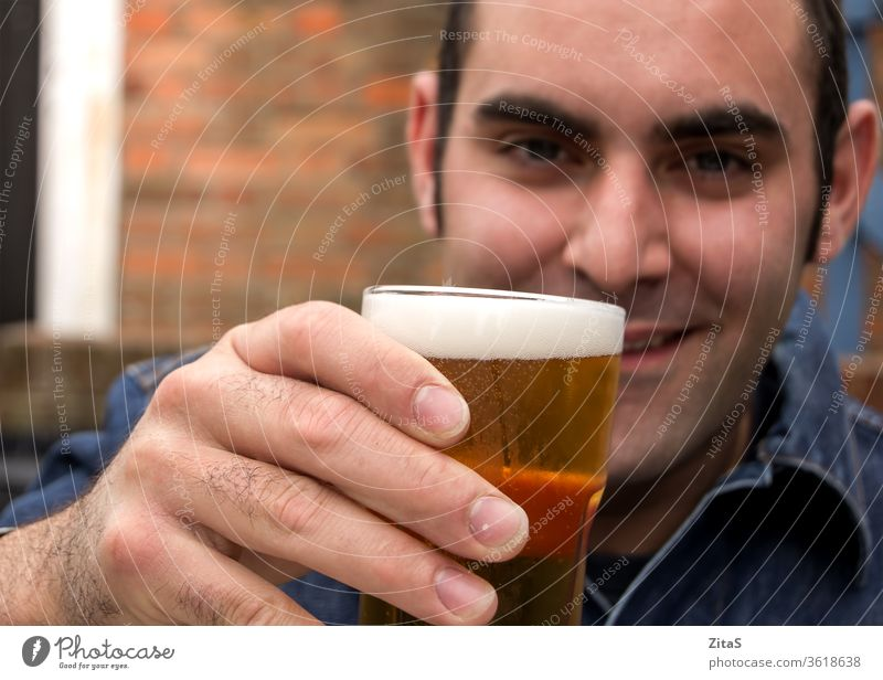 Man with beer man alcohol drink drinking pub raise glass raising hand holding male alcoholic happy relaxing chilling cold beverage addiction social party cheers
