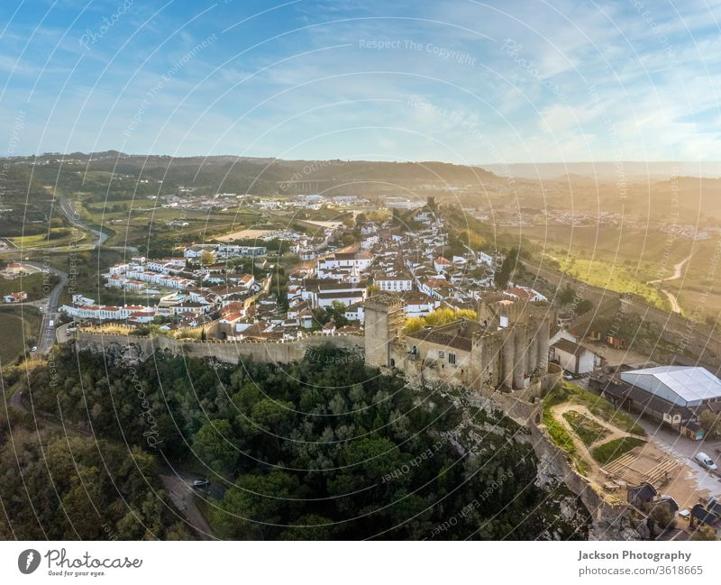 Aerial shoot of Obidos with historic walls and castle, Portugal obidos aerial portugal leiria myth fairy tale green sky yellow copy space sunset