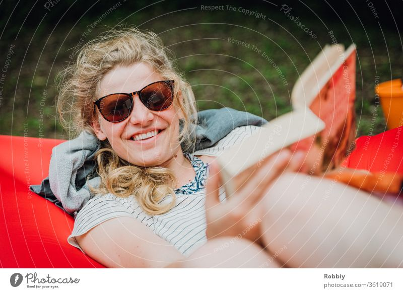 Young woman reading a book while lying on a lamzac on vacation and smiling friendly into the camera Book Reading Literature Lie Smiling Sunglasses relax chill