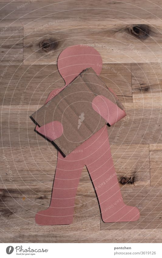 Man of paper holds a piece of empty cardboard, cardboard in front of his body. Space for text . package . parcel carrier. Demonstration Cardboard paperboard