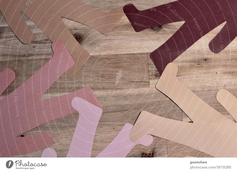 Lower bodies of people made of paper with different skin colours lie foot to foot in a circle. Diversity, cohesion, peace, friendship Skin color lower body