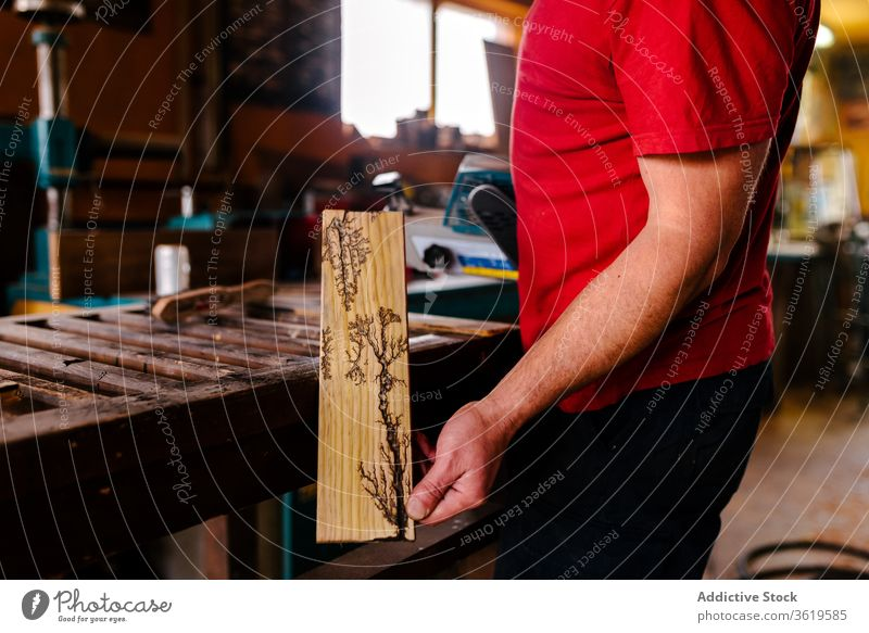 Male woodworker with decorated wooden plank workshop pyrographer pyrography man artisan craftsman decoration male woodburning job professional occupation stand