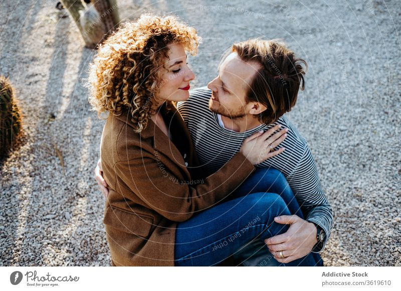 Happy couple hugging in cactus park love happy sunny daytime barcelona spain man woman excited relationship embrace cheerful summer together smile rest romantic