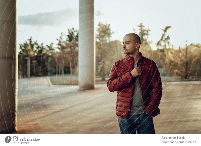 Young man in trendy outfit standing on street young modern confident jacket warm clothes pensive hipster unshaven autumn beard thoughtful think bald male