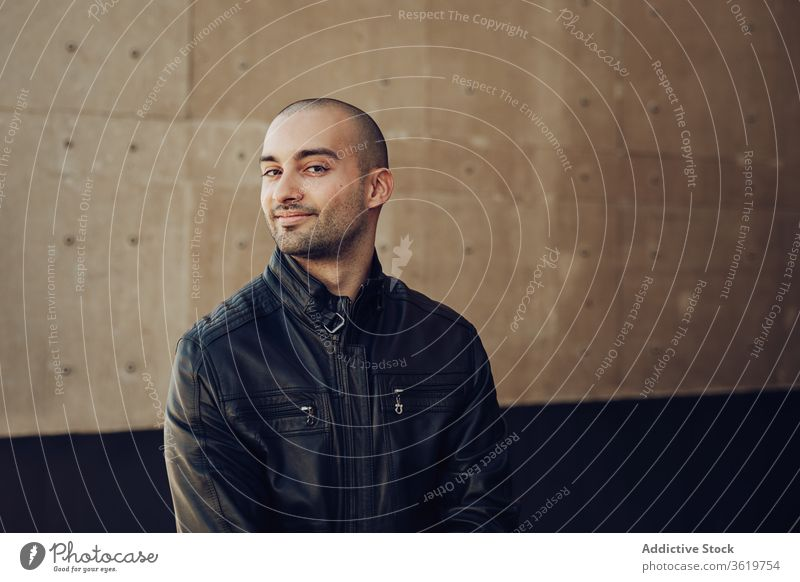 Stylish young man standing near building confident style casual modern bald wall urban street male black jacket trendy guy contemporary handsome happy fashion