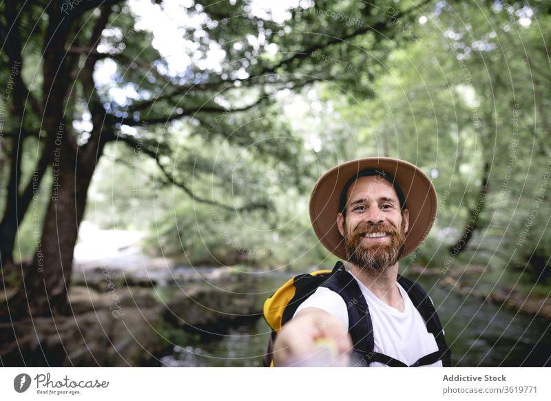 young man with beard hiking along a lake route with trees and shaded areas taking a selfie travel nature adventure outdoor lifestyle landscape mountain tourism