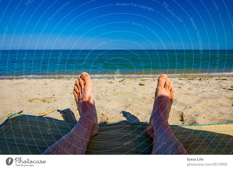 Man's legs on the beach, relaxing by the sandy beach Adult Beach Calm Carefree Coast Coastline Colorful Enjoy Feet Foam Foot Holiday Idyllic Laying Down Legs