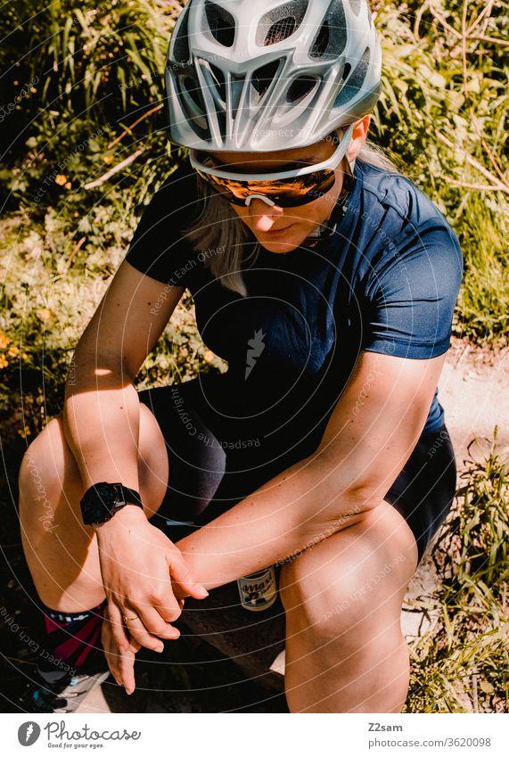 Young woman takes a break while mountain biking Woman Sports Athletic Jersey Helmet mtb Cycling cycling Sunglasses Fashion Sit Meadow rest Break athlete