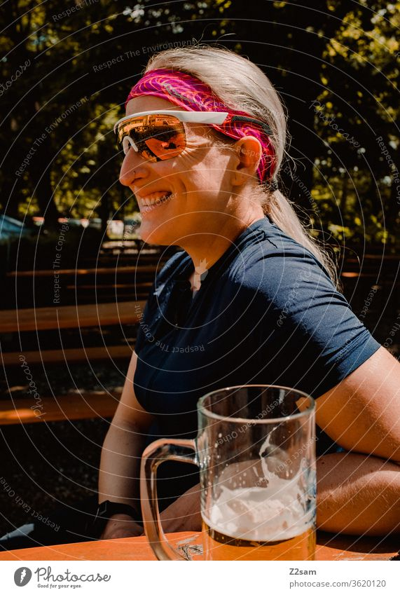 Bike tour break in the beer garden Bavaria Beer garden Shandy Drinking To enjoy relax Laughter cheerful fortunate relaxed Athletic Jersey sunglasses Young woman